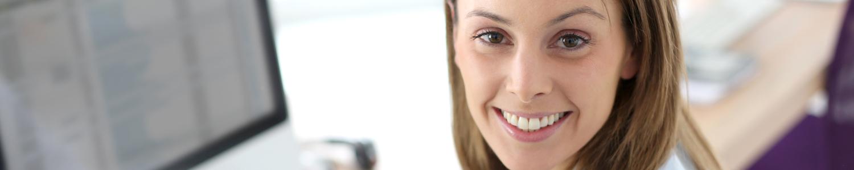 Headerbild Frau lächelt am Arbeitsplatz