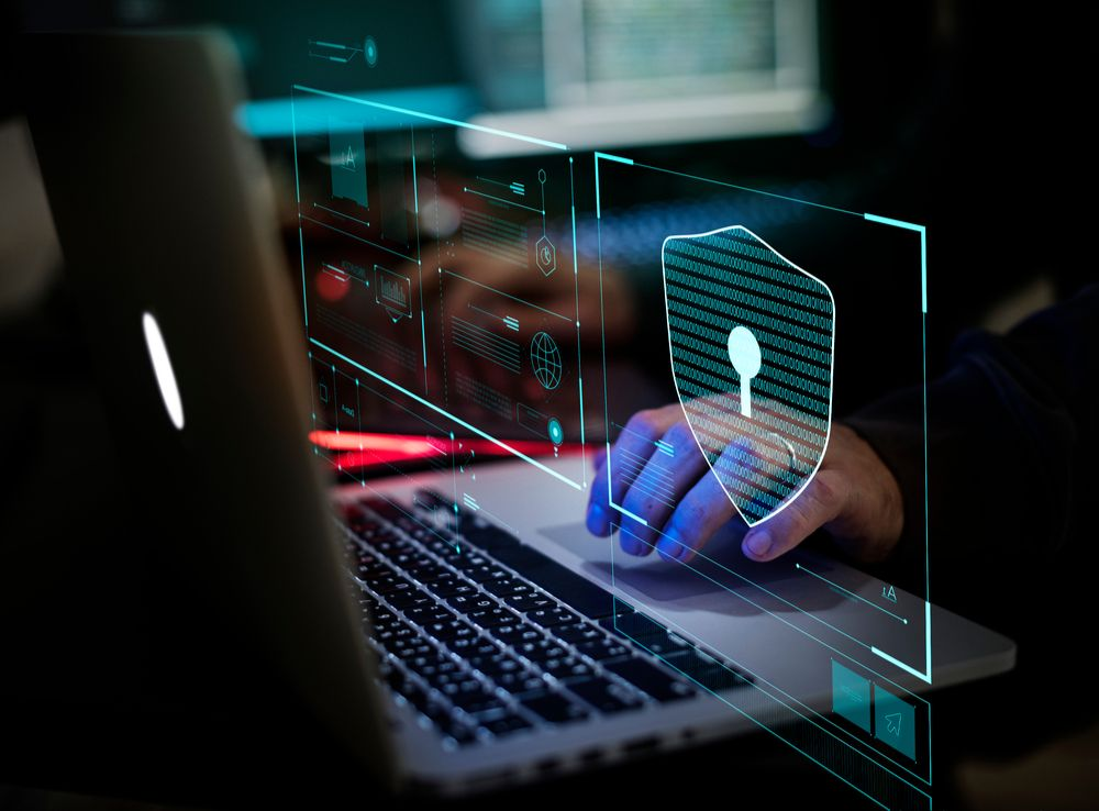 Hände auf einem Laptop in blauen Licht mit digitalem Schloss